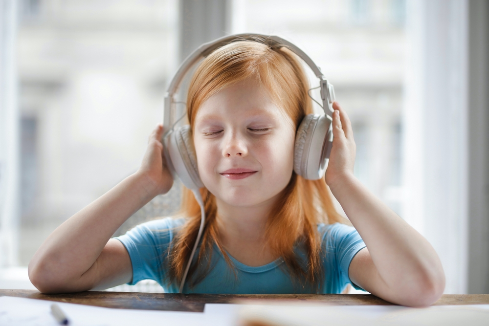 Photo d'une petite fille qui écoute de la musique pour illustrer la reprise des activtés musicales à distance avec des tout petits