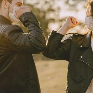 photo de deux personnes qui se saluent avec le coude dans le respect des gestes barrières